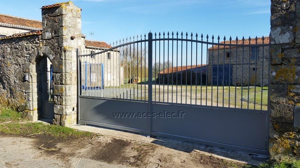 Menuiseries : installation de Portail électrique aluminium traditionnel pivotant ajouré aspect fer forgé RAL 7037 avec automatismes enterré, télécommande et portier vidéo à Mauléon